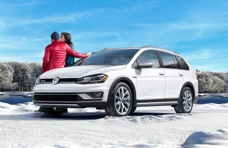 Front driver angle of a white 2019 Volkswagen Golf Alltrack parked in snow and a couple leaning on its passenger side