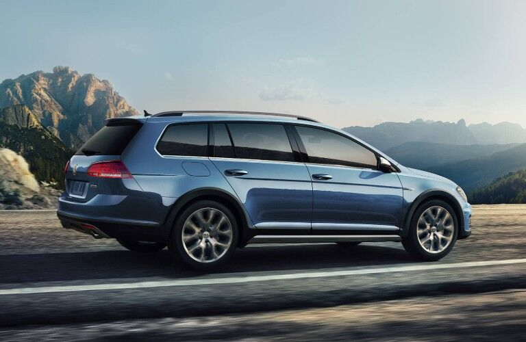 Passenger angle of a blue 2019 Volkswagen Golf Alltrack driving down a road