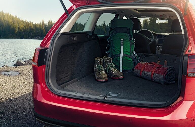 Rear view of the back of a red 2019 Volkswagen Golf Alltrack opened with the rear seats down and outdoor gear inside