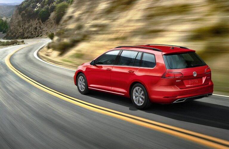 Rear driver angle of a red 2019 Volkswagen Golf SportWagen driving down a road