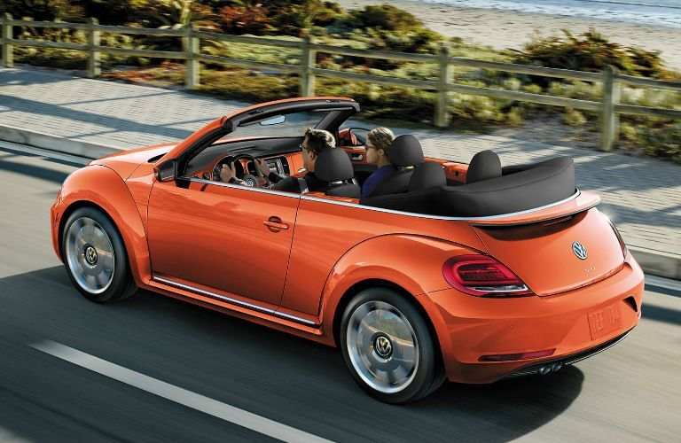 Orange 2019 Volkswagen Beetle Convertible driving on a coastal road