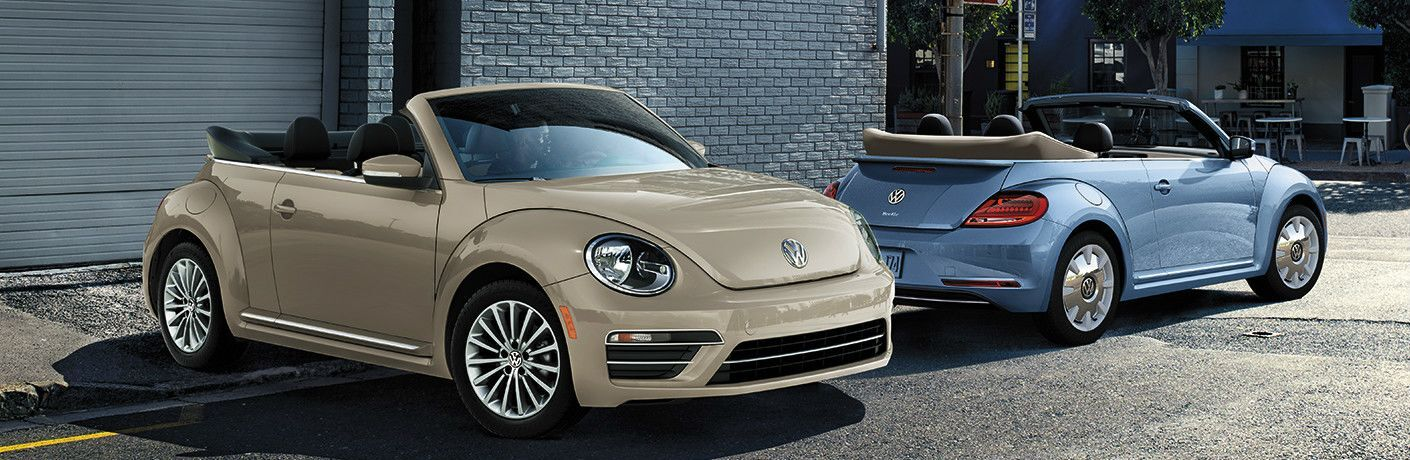 Two 2019 Volkswagen Beetle Convertible vehicles parked next to a brick building