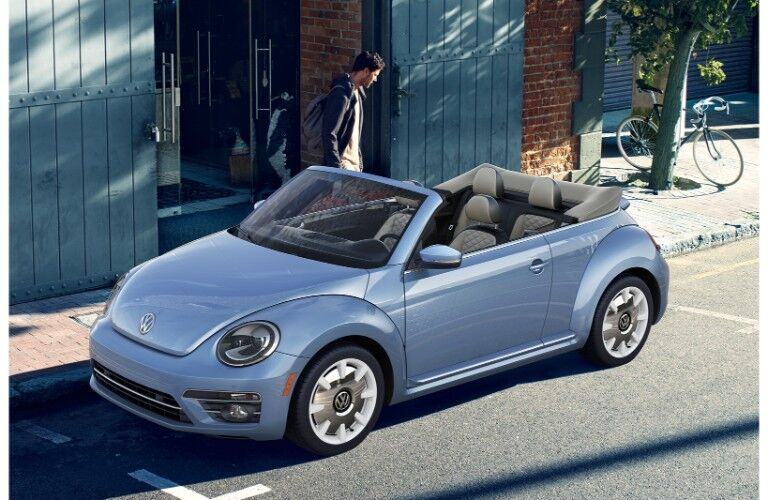 2019 Volkswagen Beetle Final Edition convertible exterior shot with blue paint job parked next a wood and brick building near a bike