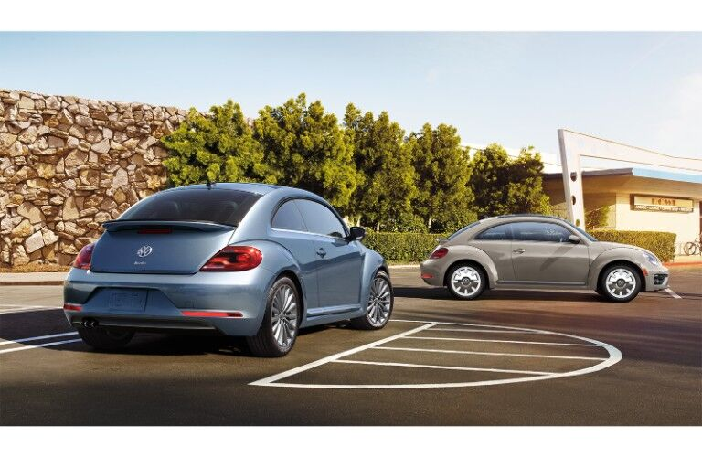 2019 Volkswagen Beetle Final Edition coupe models exterior shot with blue and beige paint colors parked near a stone wall and shrubbery