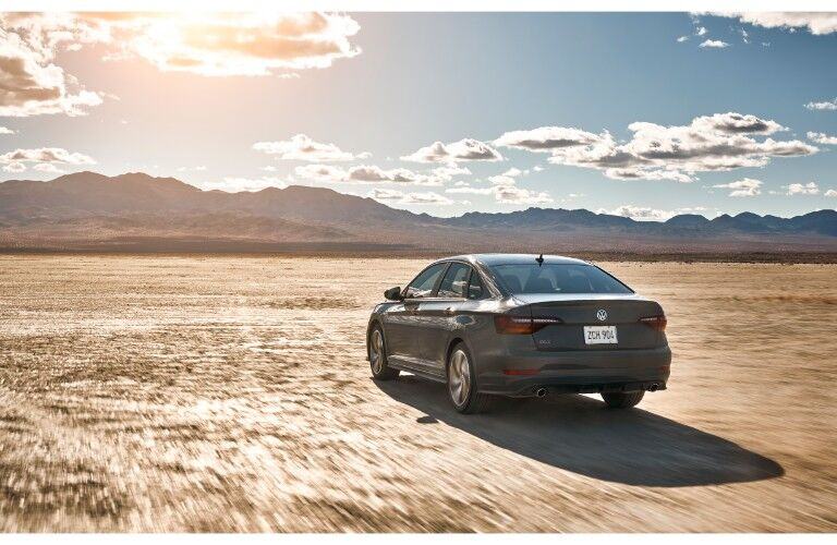 2019 Volkswagen Jetta GLI performance sedan exterior rear shot driving across a desert plain into the direction of a bright sun in the blue cloudy sky