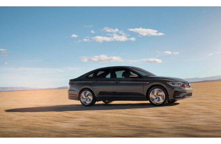 2019 Volkswagen Jetta GLI performance sedan exterior side shot driving across a desert plain