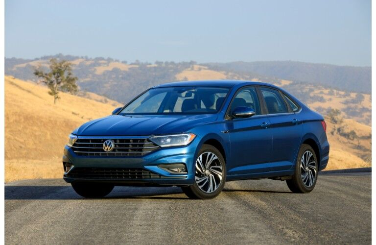 2019 Volkswagen Jetta exterior blue parked in the middle of a bright desert highway