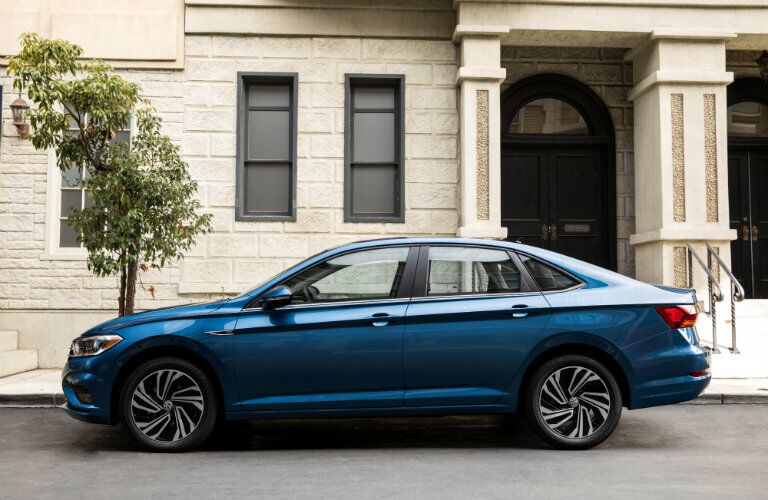 2019 Volkswagen Jetta exterior side shot length blue paint parked next to a fancy house