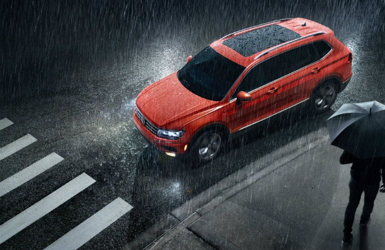 2019 Volkswagen Tiguan exterior overhead shot with red color paint job stopped at a crosswalk during a rain shower with headlights on