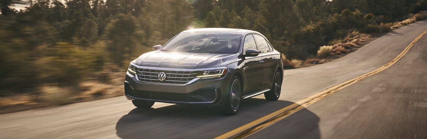2020 Volkswagen Passat redesign exterior shot with gray paint color driving through a forest road under the glare of a setting sun