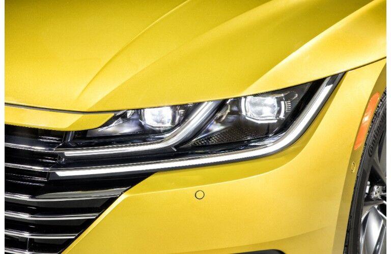 exterior closeup shot of 2019 Volkswagen Arteon LED headlight design with yellow body paint color
