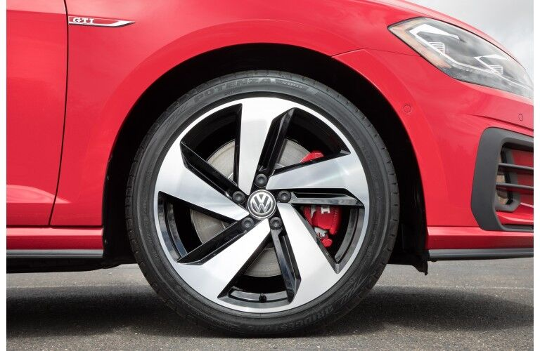 2019 Volkswagen Golf GTI exterior closeup shot of wheel and tire design alongside red paint color