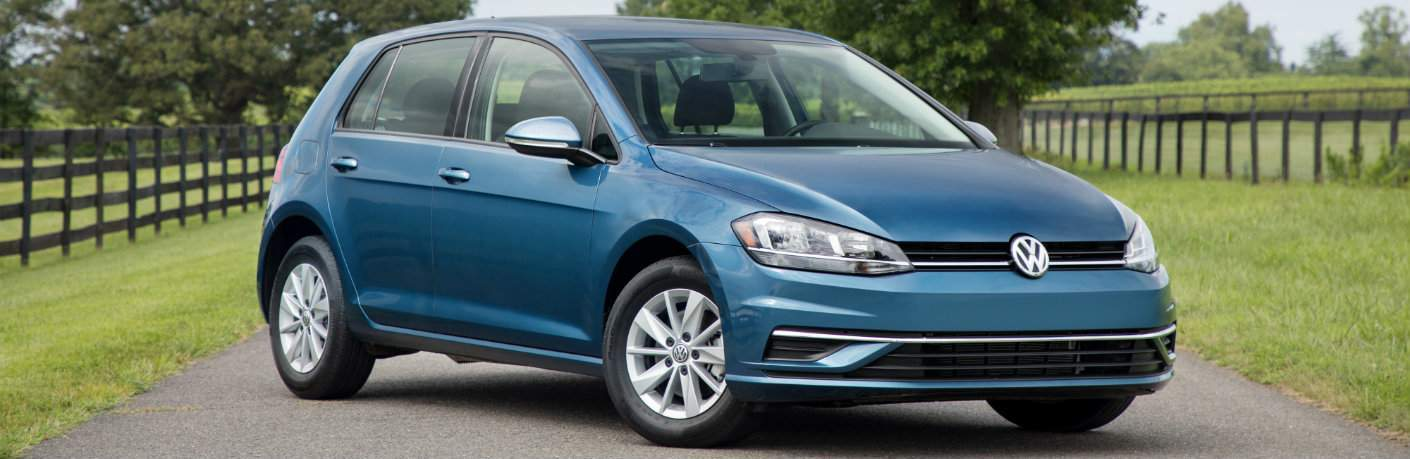 Blue 2018 Volkswagen Golf on rural road surrounded by fences