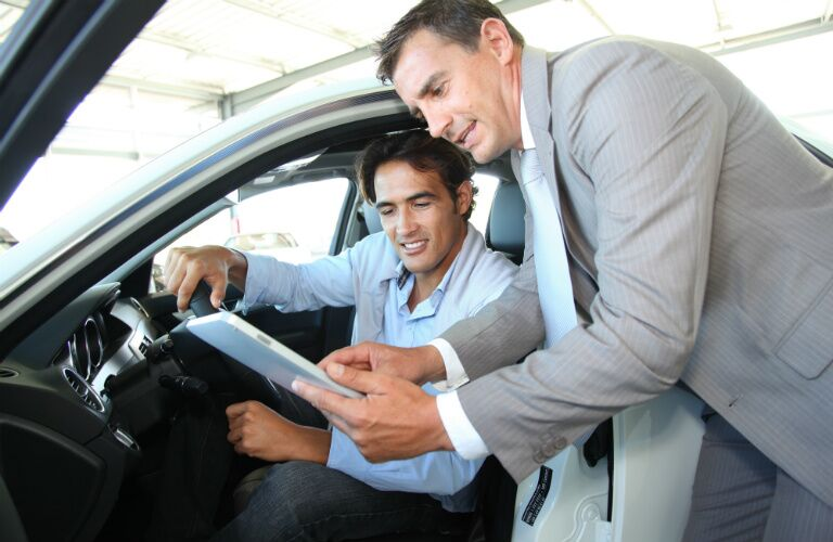 car sales person showing man new car specs
