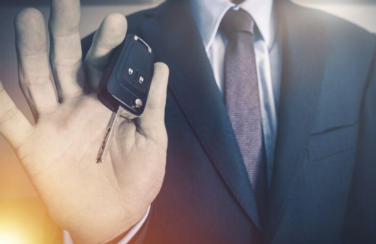 car dealer giving car keys to driver