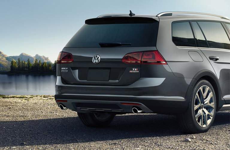 Rear end of black 2018 Volkswagen Golf Alltrack parked in front of mountain lake