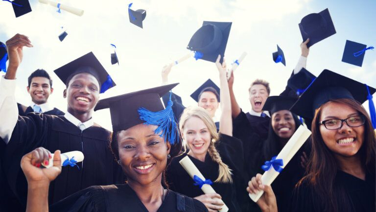college graduates celebrating by throwing blue tassel graduation caps in the air