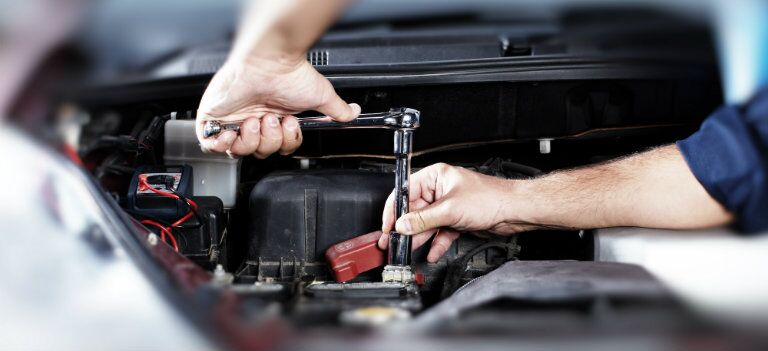 using a wrench to repair a volkswagen in service department