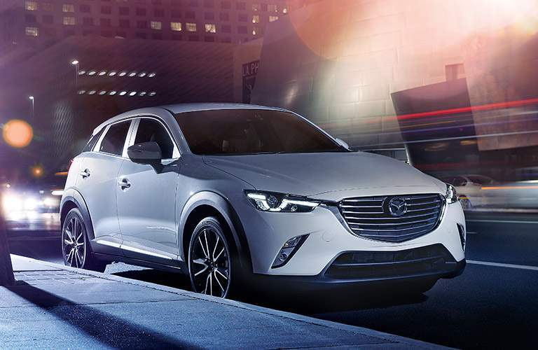 Mazda CX-3 Parked on Street at Night with Headlights Illuminated in White Exterior Color