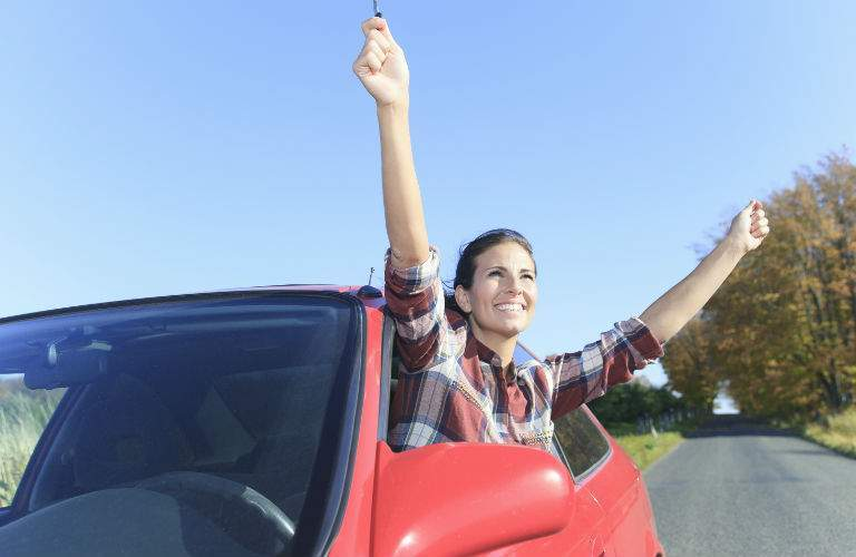 Woman in Drivers Seat of Used Car Looking Happy
