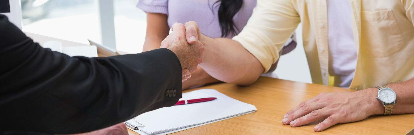 Couple Shaking Hands with Used Car Salesperson
