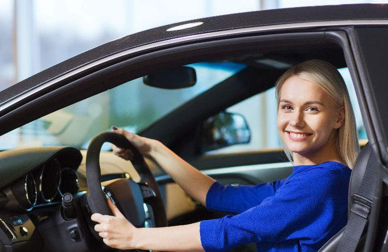 Woman Sitting in Used Car Looking Happy