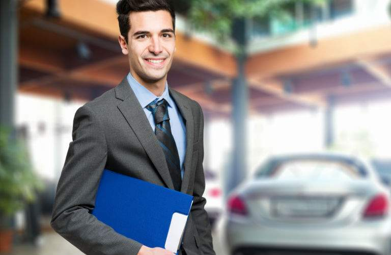 Used Car Dealer with Paperwork in Hand