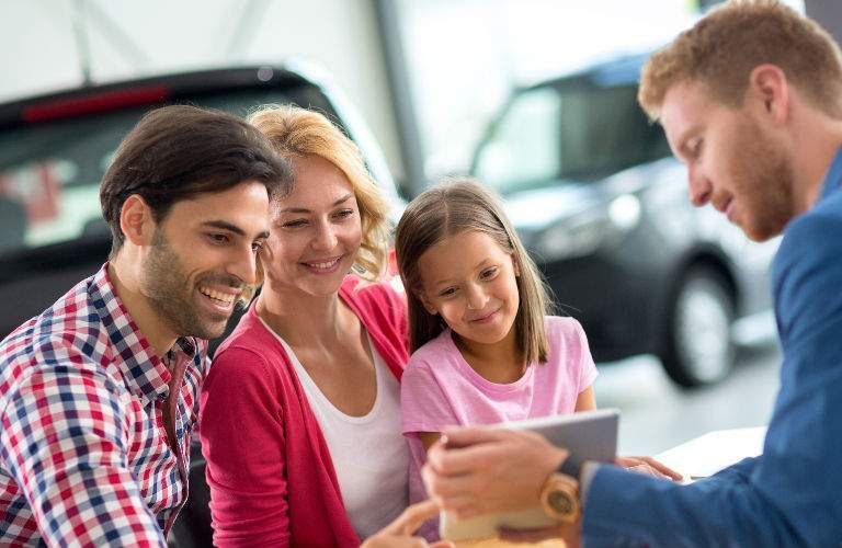 Family Talking with Used Car Dealer