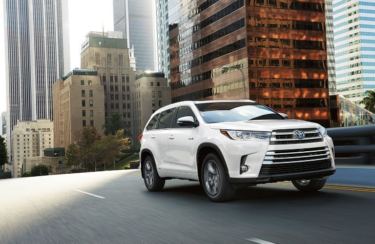 White 2017 Toyota Highlander Driving Down Urban Street