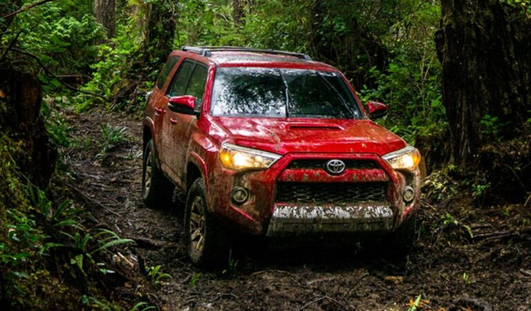 Toyota 4Runner Exterior View in Red Driving Off-Road through Wooded Area
