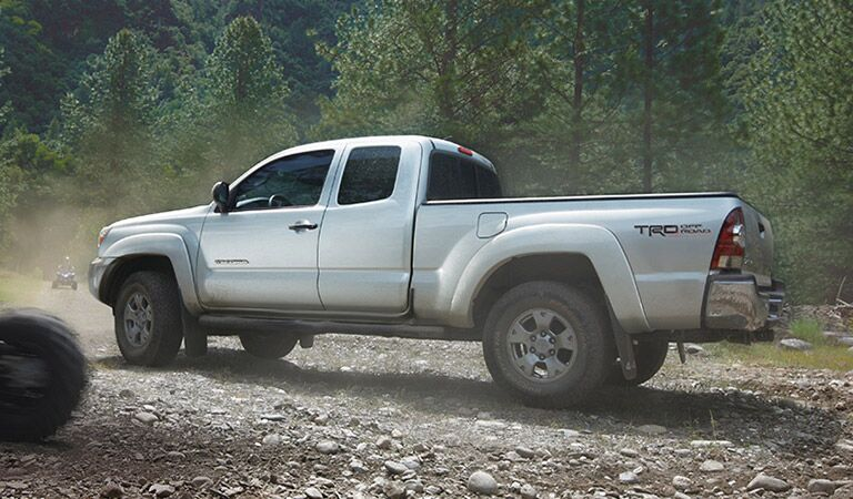 Toyota Tacoma Driving on Gravel Road Side View in Silver