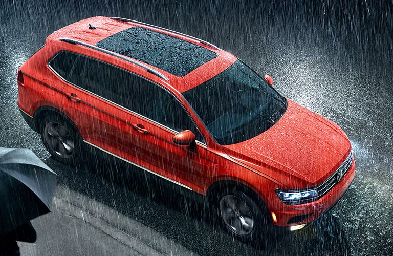 Front passenger aerial angle of an orange 2019 Volkswagen Tiguan parked on the side of the road in the rain