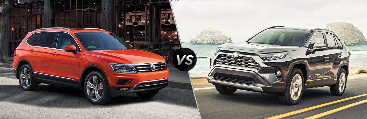 Front passenger angle of an orange 2019 Volkswagen Tiguan on left VS front driver angle of a black 2019 Toyota RAV4 on right