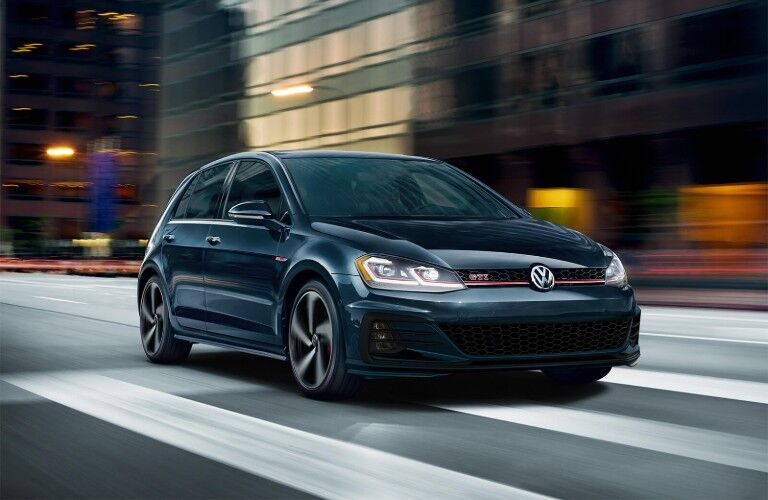 Front passenger angle of a green 2019 Volkswagen Golf GTI driving on a city road