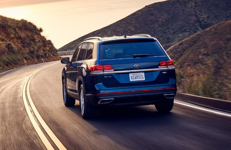 2021 Volkswagen Atlas exterior rear shot driving on a grassy mountain highway as the sun sets in the sky