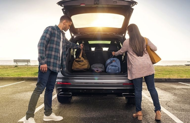 a man and a woman getting luggage out of the 2022 VW Tiguan