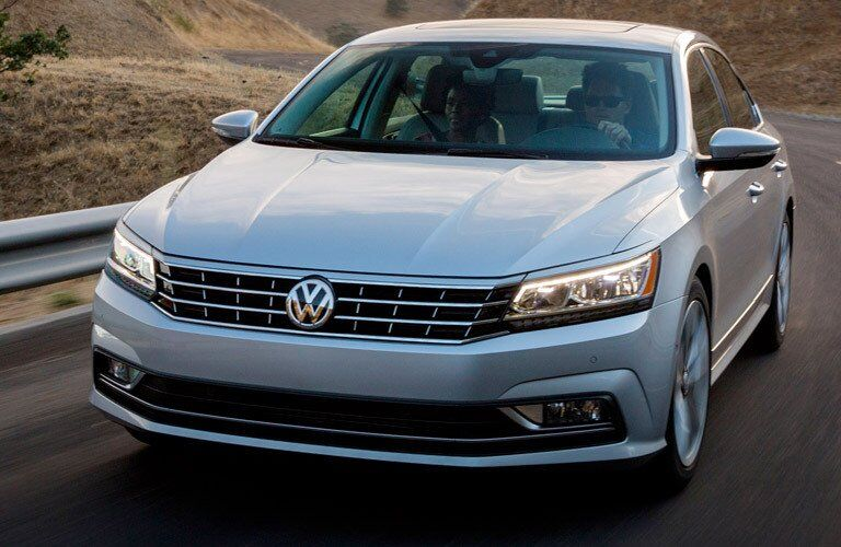 2017 Volkswagen Passat exterior gray paint front shot driving through a winding fall country road