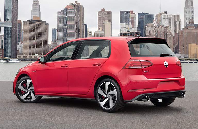 2018 Volkswagen Golf GTI rear exterior shot red paint color parked on a beach with a cityscape background