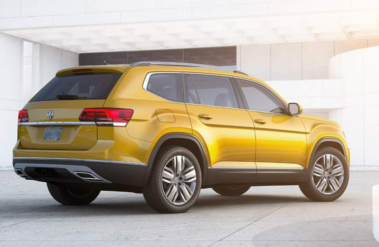 2018 Volkswagen Atlas exterior rear shot in a white room of bumper, back wheels, side doors, and trunk