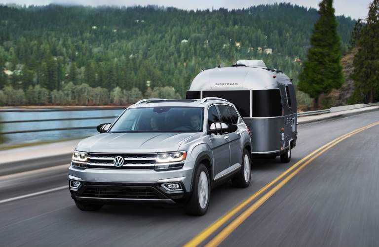 2018 Volkswagen Atlas exterior shot towing a trailer on a country highway near a forest and lake