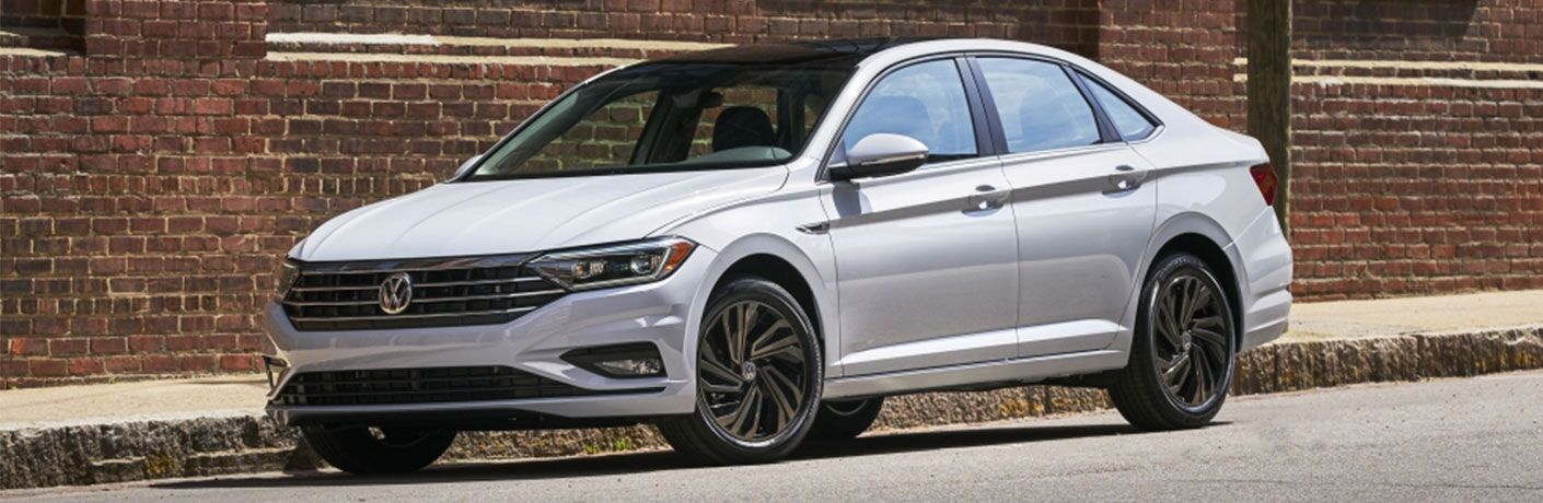 2019 Volkswagen Jetta exterior shot white paint parked on a street next to a red brick building