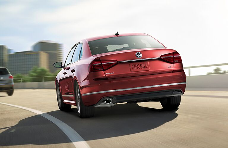 2019 Volkswagen Passat exterior rear shot with red paint color driving under the sun on a highway