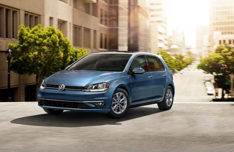 2019 Volkswagen Golf exterior shot with blue paint color driving through a suburban city neighborhood under the sun