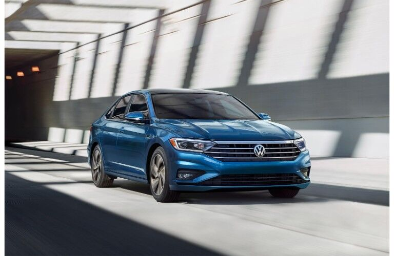 2019 Volkswagen Jetta exterior shot blue driving through a tunnel with sun and shadow surrounding it