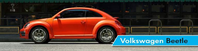 A profile view of a VW Beetle in Orange that is for sale at Vic Bailey Volkswagen