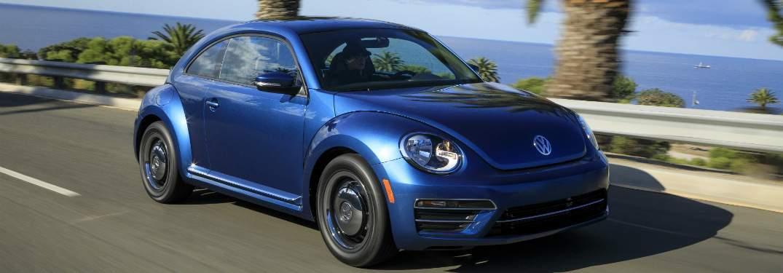 blue 2018 volkswagen beetle driving on coastal highway