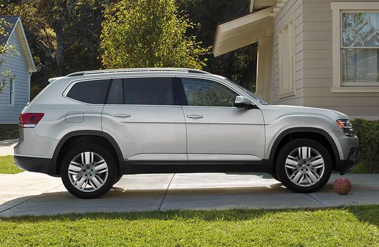 2019 Volkswagen Atlas exterior side shot with beige paint color parked on the driving of a house next to a lawn and basketball