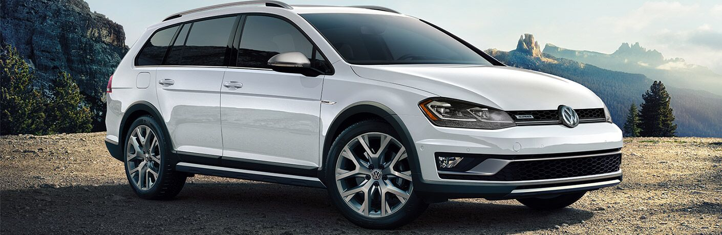 2019 Volkswagen Golf Alltrack exterior shot with white paint color parked on a gravel mountain cliff with fog in the background