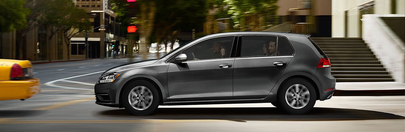 2019 Volkswagen Golf exterior side shot with gray paint color driving through a city behind a taxi and near a set of steps