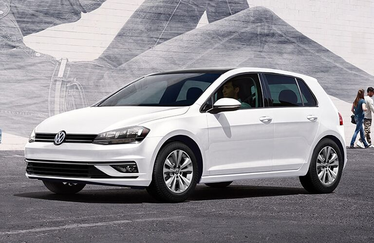 2019 Volkswagen Golf exterior shot with white paint color parked in front of a large wall mural with graffiti